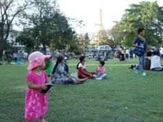 芝生に座ってくつろぐ人たち